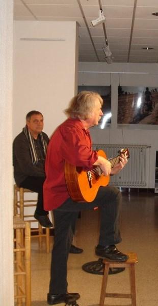 Michel Grange à la guitare, Gilles Cherbut assis le regarde